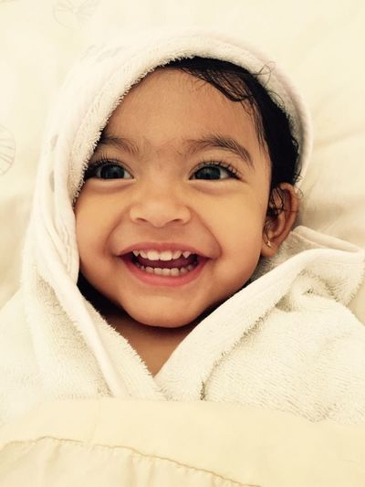 Close-Up Of Cute Baby Girl Wrapped In Towel