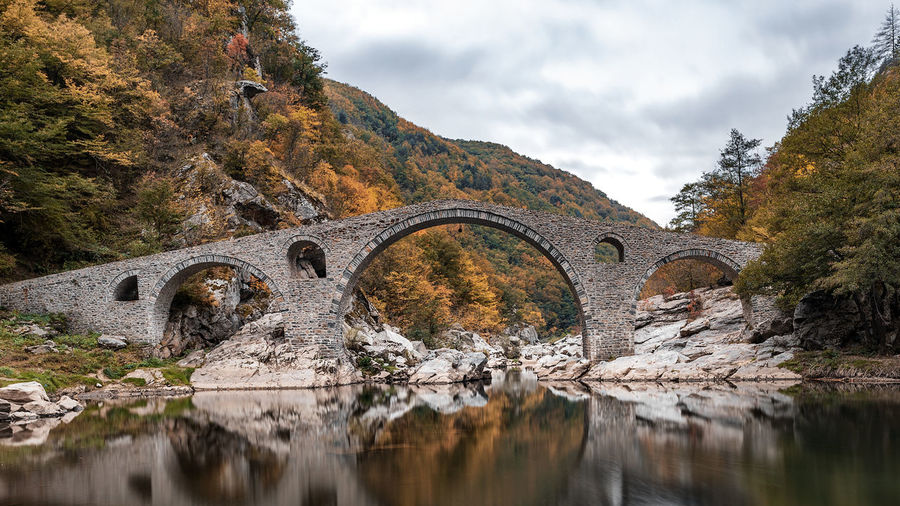 Devil's bridge, Bulgaria. Ancient stone bridge over Arda river, autumn time with leaves in water. Rhodope mountain Water Arch Bridge Reflection Connection Bridge - Man Made Structure Bridge Arch Nature River Sky Built Structure Architecture Waterfront Outdoors Autumn Devil Bulgaria Arda Ardino Forest Destination Travel Tourism Rhodope Mountains Cloud - Sky