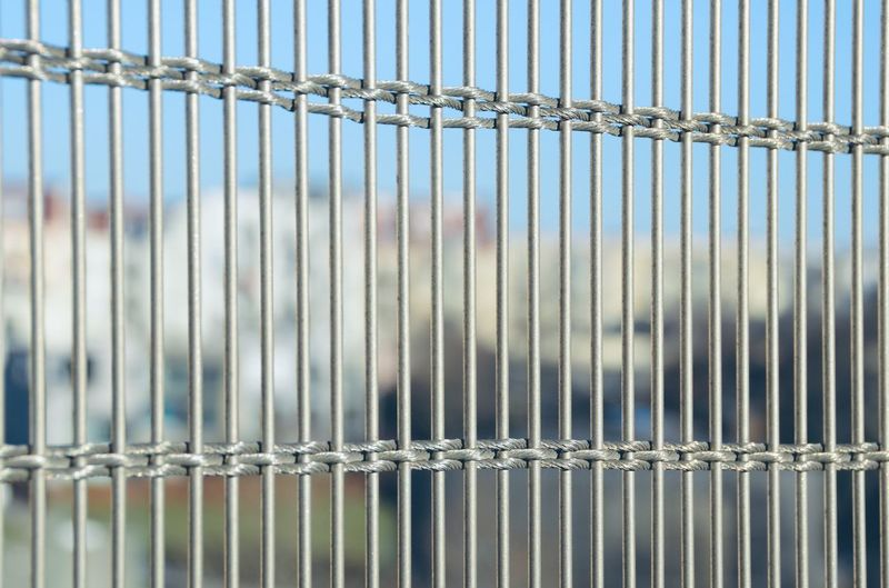 Full frame shot of metal fence against wall