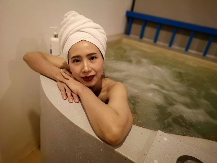 Portrait Of Shirtless Mature Woman Sitting In Hot Tub At Health Spa
