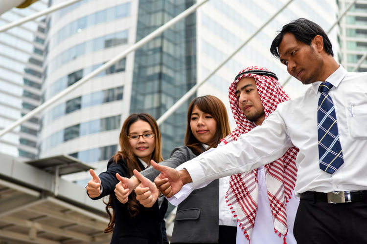 Low angle view of colleagues showing thumbs up against skyscraper in city