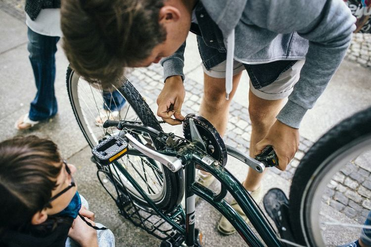 High Angle View Of Man Repairing Bicycle On Street