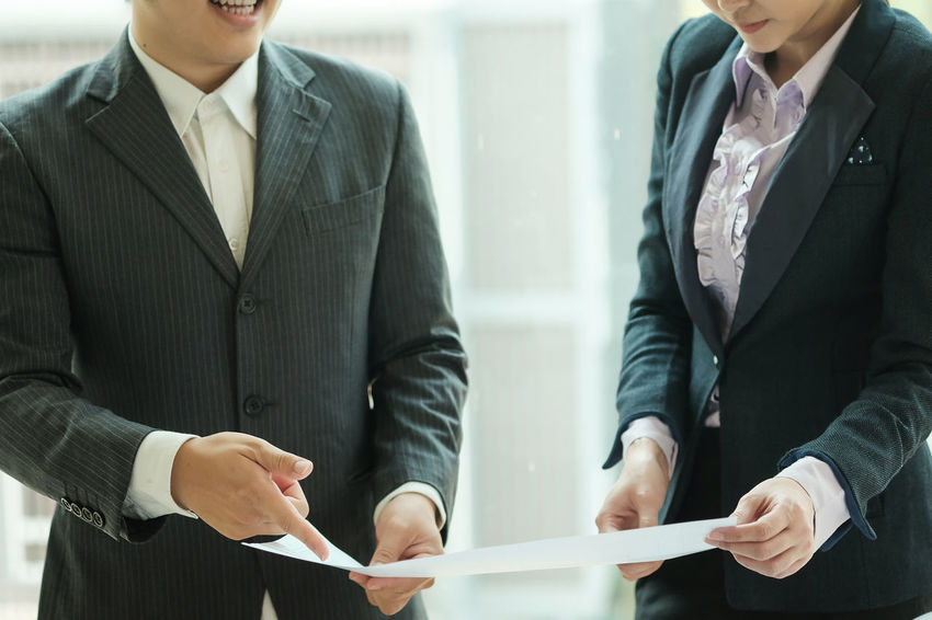 Two business man and women are talking about something on paper, Business and financial concept, closed up. Business Business Concepts Business Person Businessman Businesswear Businesswoman Close-up Conference Coorperation Corperation Corporate Business Discussion Holding Human Hand Meeting Men Occupation Office Suit Talking Pictures Teamwork Two People Working
