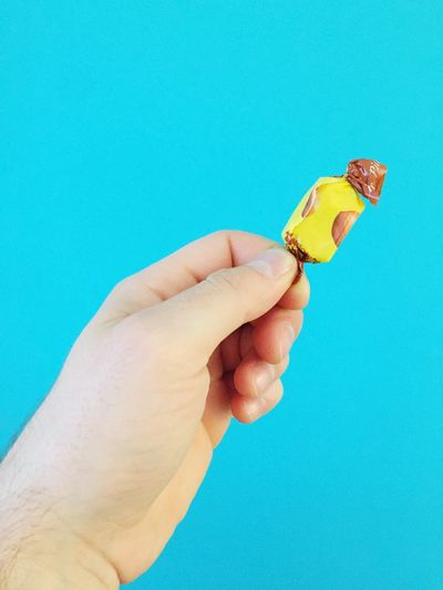 Cropped hand holding chocolate against blue background