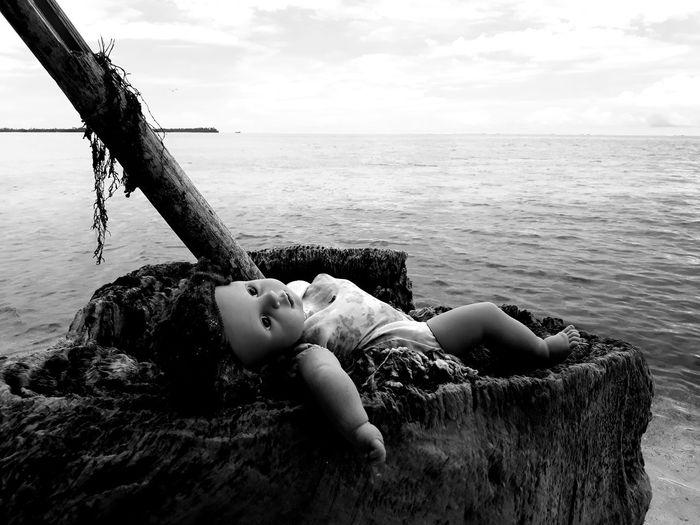 Doll lying in sea against sky