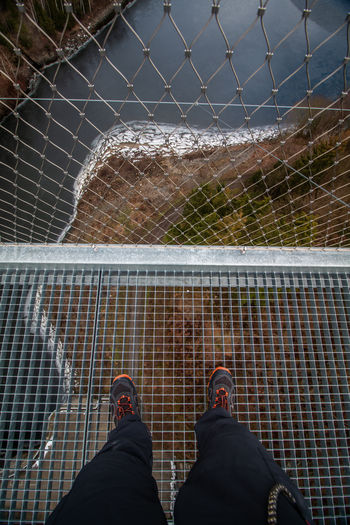Low section of person standing on fence over river