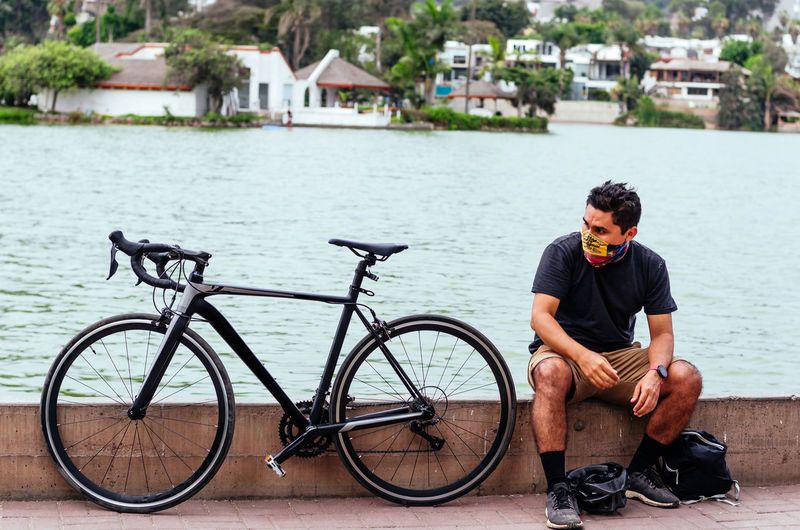 Young man sitting on bicycle by water