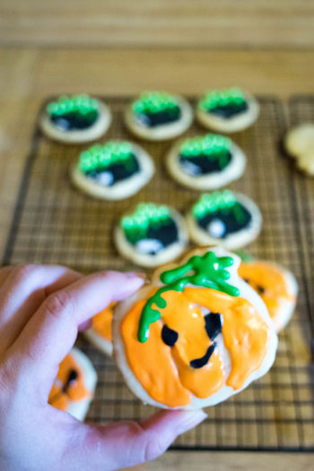 Baked Goods Cookies Halloween Halloween Treats SugarCookies Treats Close-up Day Dessert Festive Focus On Foreground Food Food And Drink Freshness Human Body Part Human Hand Indoors  Lifestyles Multi Colored One Person Ready-to-eat Real People Sugar Cookies Sweet Food Table