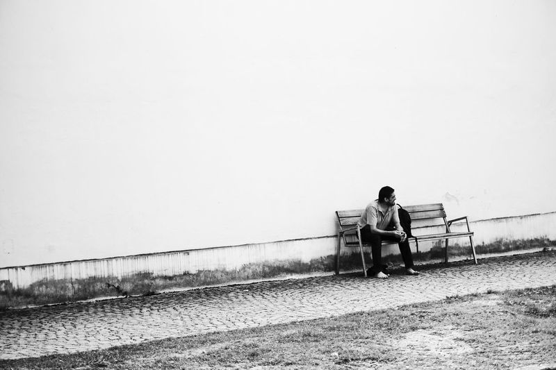 Man Sitting On Bench Against Wall