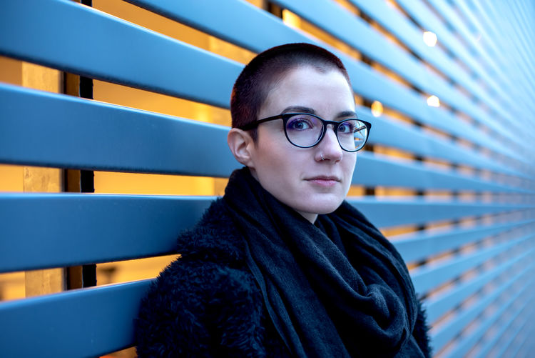 Emotional cool toned portrait of a short haired young woman wearing glasses and an elegant black coat. Portrait Eyeglasses  Glasses Looking At Camera One Person Lifestyles Headshot Real People Young Adult Front View Leisure Activity Waist Up Clothing Casual Clothing Architecture Young Men Focus On Foreground Men Scarf Contemplation Teenager
