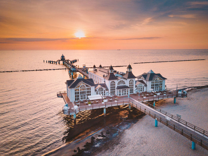 Drone view of stilt houses on pier over sea against sky during suset