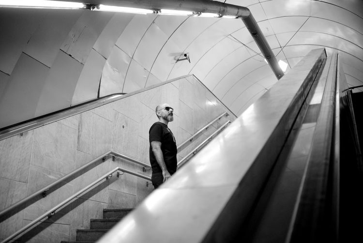 The Architect - 2019 EyeEm Awards EyeEm Best Shots Eye4photography  Getting Inspired My Best Photo Underground Notes From The Underground The Portraitist - 2019 EyeEm Awards Real People Indoors  One Person Portrait Blackandwhite Monochrome Staircase Architecture Men Standing Steps And Staircases Full Length Lifestyles Transportation Low Angle View Illuminated Built Structure Escalator Public Transportation Moving Down Subway Ceiling Modern Moving Walkway