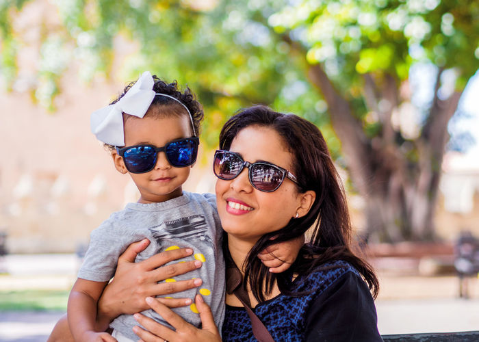 Portrait Of Smiling Mother And Daughter Wearing Sunglasses Against Trees At Park