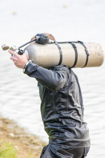 Scuba diver with cylinder at lakeshore