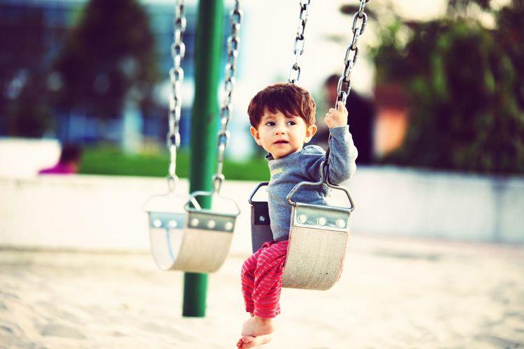 Boy sitting on swing at playground