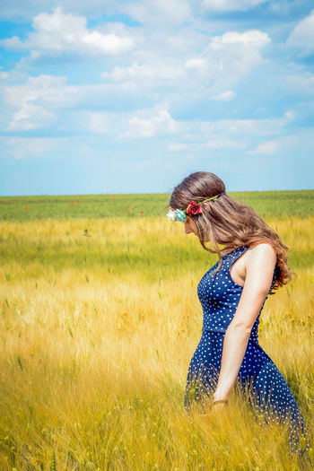 Side View Of Young Woman Standing In Field