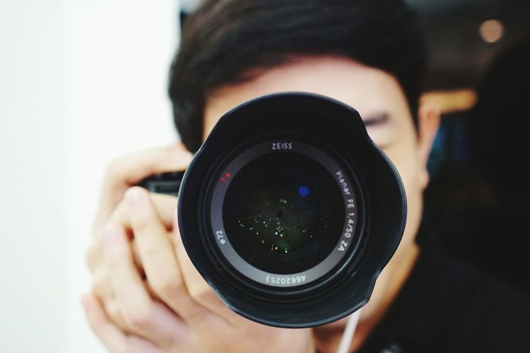 Close-up of man photographing with camera