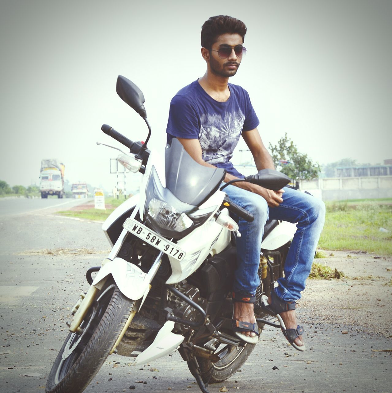 casual clothing, transportation, young adult, full length, land vehicle, young men, sitting, motorcycle, real people, mode of transport, one person, outdoors, day, scooter, clear sky, smiling