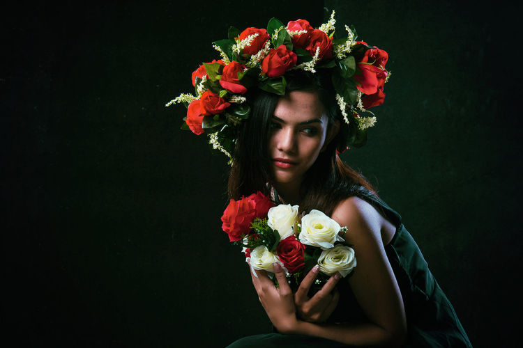 Thoughtful Female Model Wearing Flowers While Sitting Against Black Background