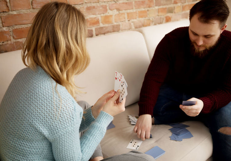 Man Playing Cards With Woman While Sitting On Sofa At Home