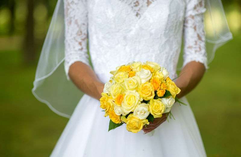 Midsection Of Bride Holding Yellow Roses Bouquet
