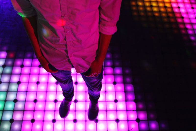 Low section of man standing on illuminated dance floor