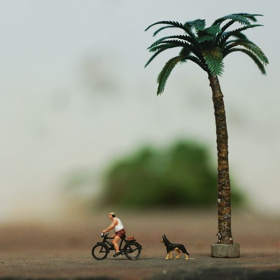 Figurine riding bicycle against sky