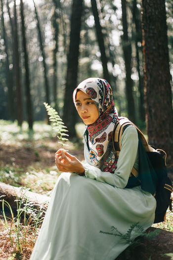 Midsection of woman holding tree trunk in forest