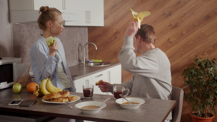 Man throwing banana while talking with wife at kitchen