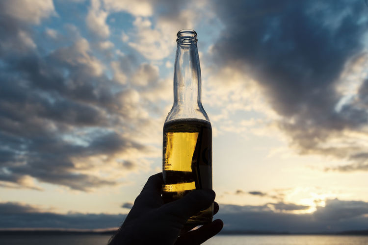 Cropped Hand Holding Beer Bottle Against Sky During Sunset