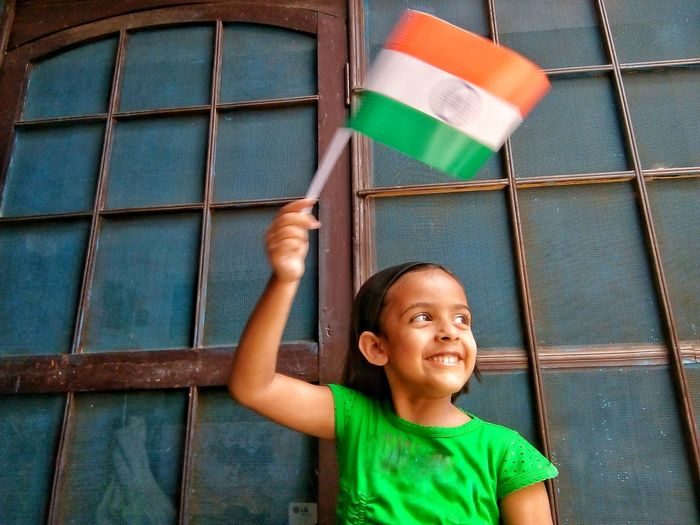 little indian girl flagging national flag Window Above HEAD Nationalism Patriotism Patriotic Girl Kid Looking Away Indian Culture  Indian Young Girl Colourful Tricolor National Nation Flag Flagging Child Human Hand Childhood Smiling Portrait Happiness Cheerful Males  Friendship Growing Blooming Festival Goer Love Is Love A New Perspective On Life