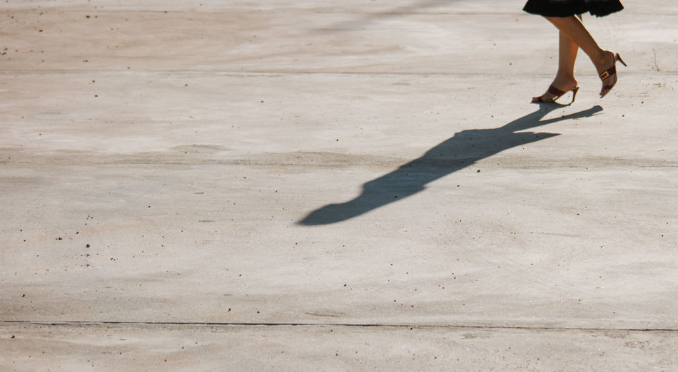 Low section of woman with shadow on concrete
