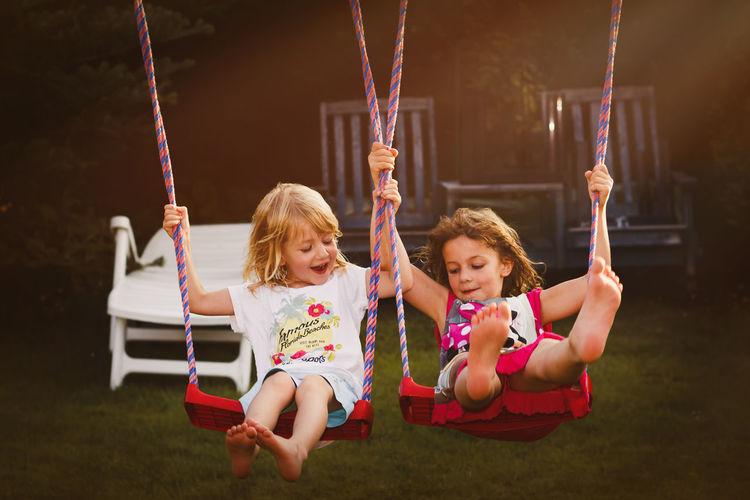 Siblings swinging at playground