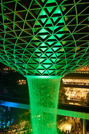 Jewel Changi Airport Water Vortex Fountain Green Color Architecture Built Structure Illuminated No People Connection Bridge Night Pattern Reflection Indoors  Nature Bridge - Man Made Structure Metal Glowing Green Ceiling Turquoise Colored