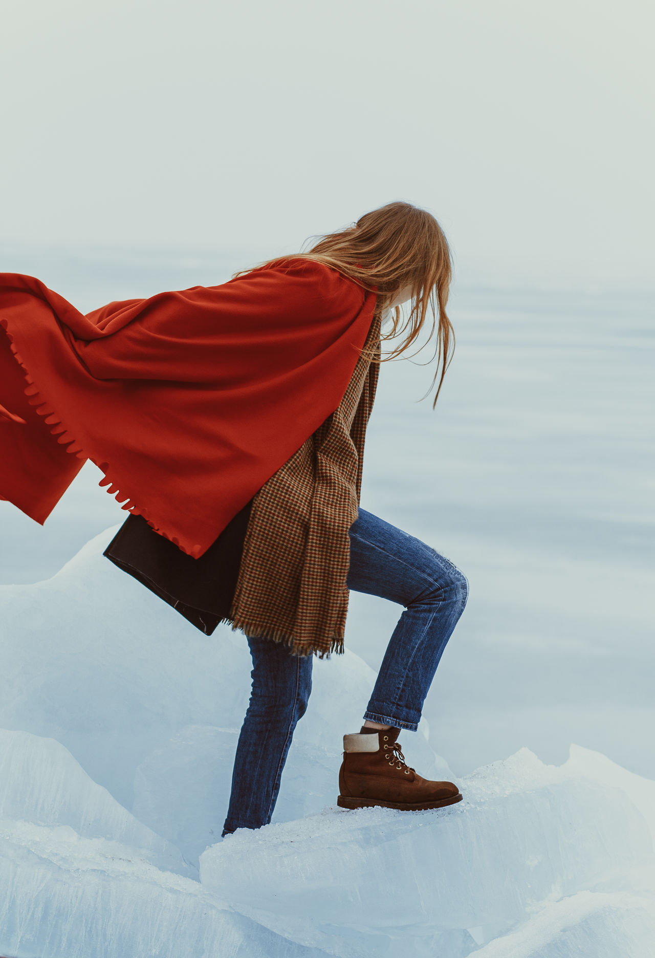 Full length of woman with red shawl standing on snow against sky