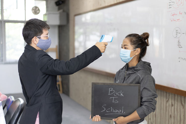 Man wearing flu mask checking temperature of woman holding slate in classroom