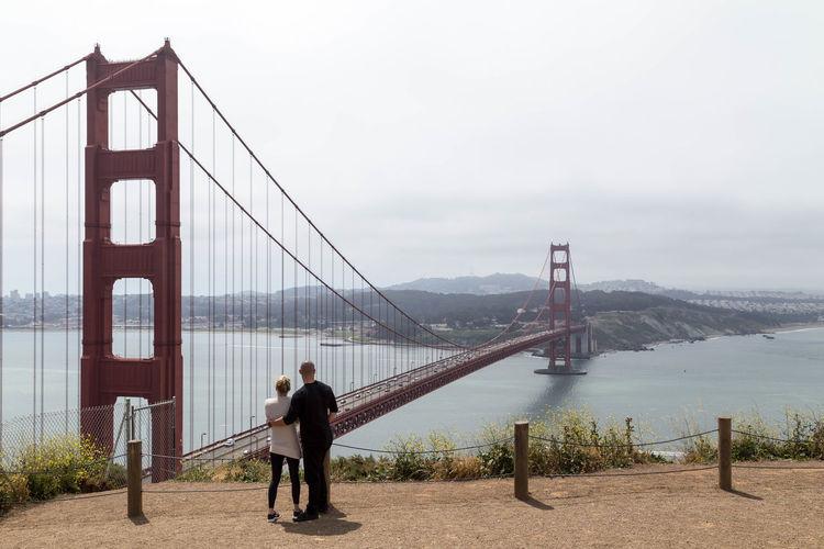 Rear view of people on suspension bridge