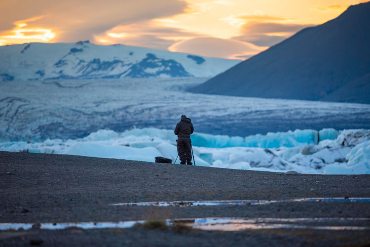 Man standing on snowcapped mountain against sky during sunset