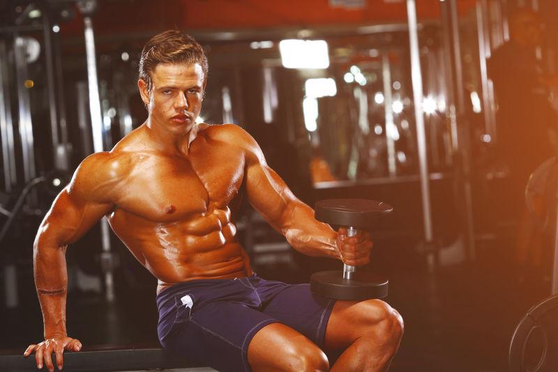 Portrait of shirtless muscular man sitting in gym