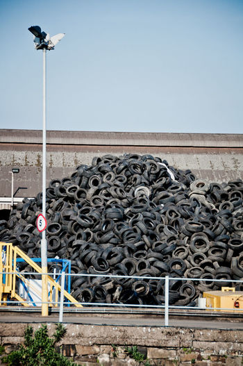 car tyre on a dumping ground Cars Copy Space Dark Dumping Ground Industry Junk Messy Wall Abstract Black Car Industry Car Tyre Chain Earthday Environmentally Harmful Metal Pattern Pile Rubber Stone Texture Tyre Tyres Waste Waste Pile