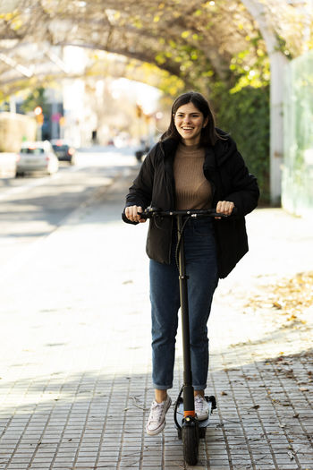 Portrait of smiling young woman standing on footpath