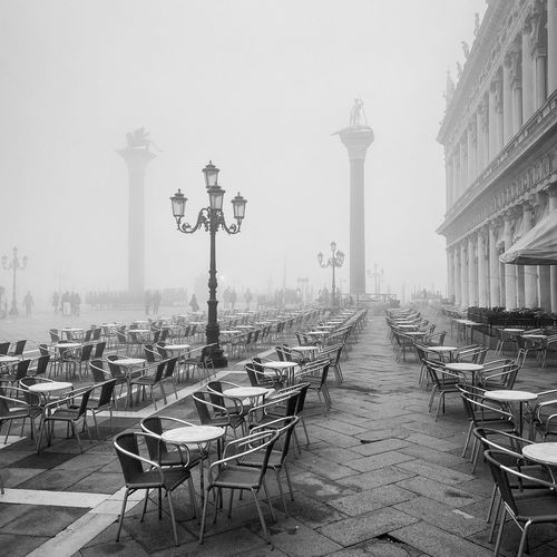 Empty chairs and tables in front of building