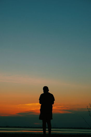 Sunset Sky Orange Color Standing Real People Silhouette Lifestyles One Person Leisure Activity Beauty In Nature Rear View Scenics - Nature Copy Space Men Nature Tranquil Scene Full Length Tranquility Land Looking At View