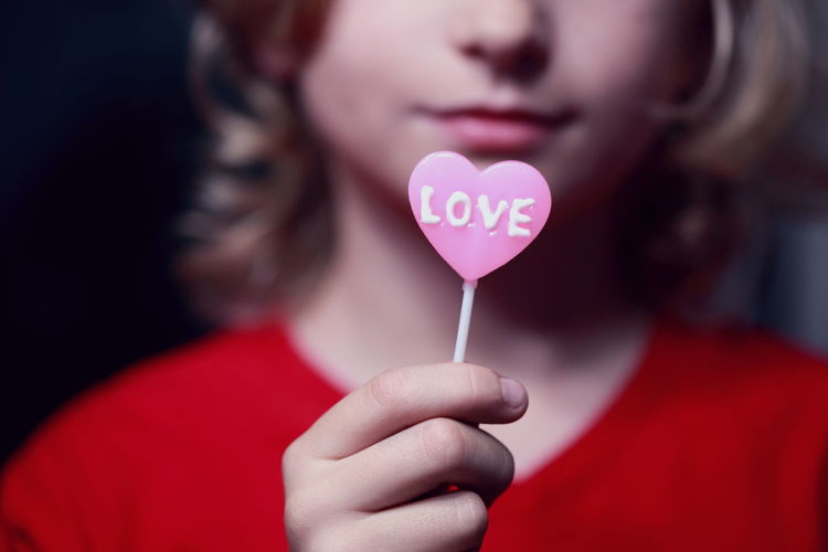 Midsection Of Girl Having Heart Shape Candy