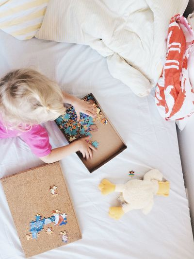 High Angle View Of Girl Playing Jigsaw Puzzle On Bed