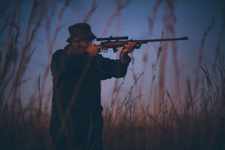 Hunter Aiming With Rifle On Grassy Field During Sunrise