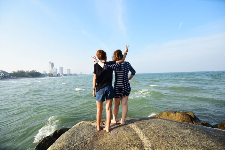 Rear View Of Friends Standing On Sea Shore Against Sky