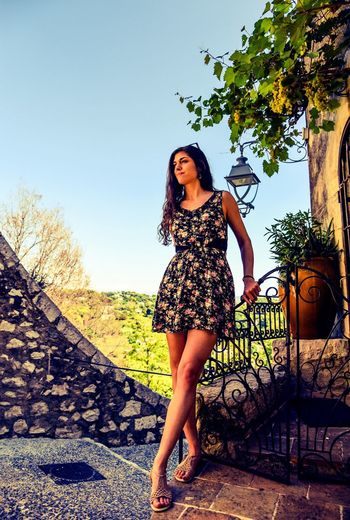 Front view of beautiful woman standing by gate against sky