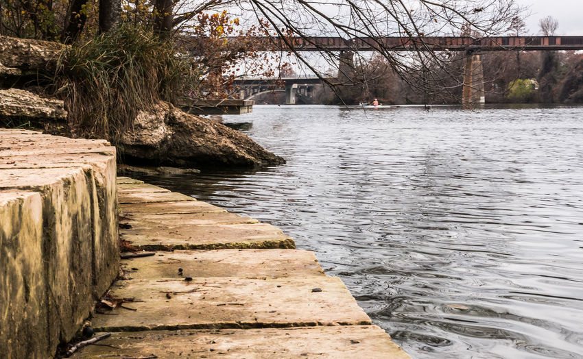 Stone ledge in Austin, Texas at the Lady Bird Lake. Architecture Beauty In Nature Bridge Built Structure Connection Day Direction Footpath Nature No People Outdoors Plant River Tranquility Tree Water Wood - Material
