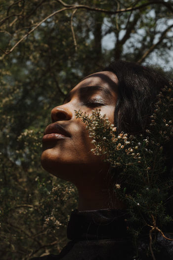 Close-up of young woman with eyes closed by plants